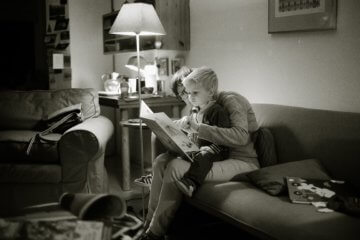 black and white photo of a parent reading to a child in their home