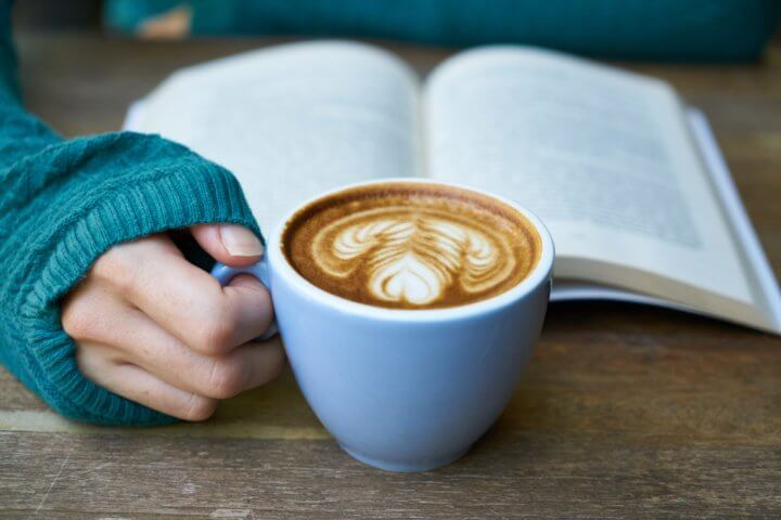 Open book on a table with a woman in a sweater holding a latte