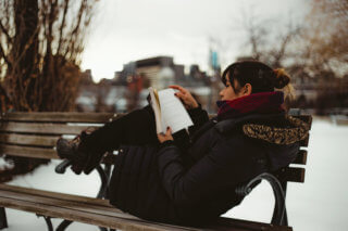 girl reading on a bench in the snow with a coat
