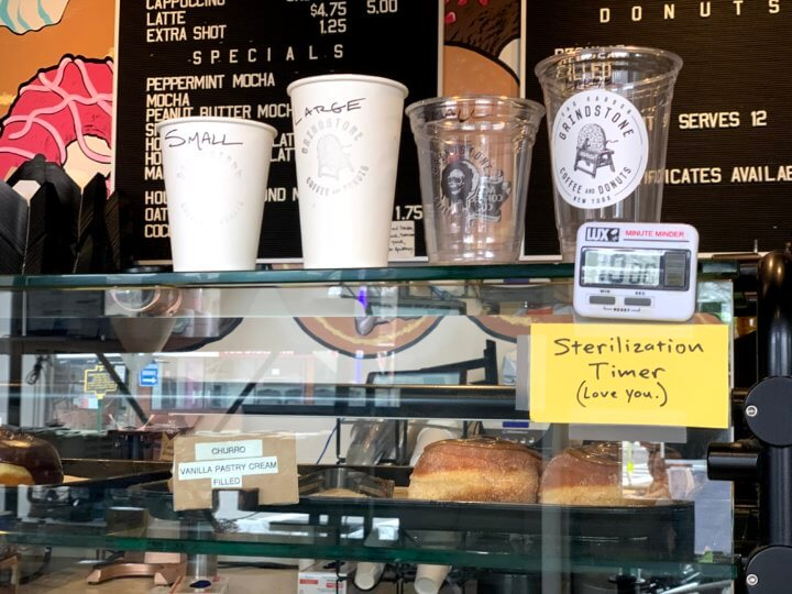 """Photograph of the counter at Grindstone Coffee & Donuts. There is a timer next to the sample sizes of cups with a post-it that reads """"Sterilization Timer (Love you)."""""""