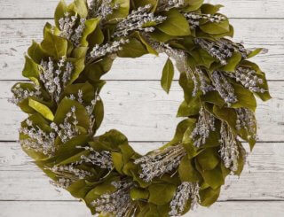 A wreath alternating straight green leaves and lavender sprigs on a white wood background.