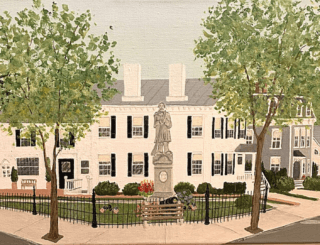 A statue and WW2 memorial of Sag Harbor in front of a white house framed by a black fence and green leafy trees.