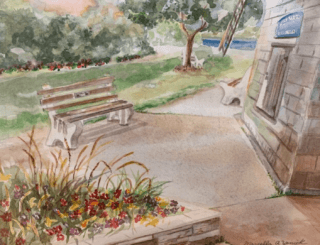 A bench next to the base of the Sag Harbor mill, in pastel shades with red, orange, and yellow flowers in the foreground.
