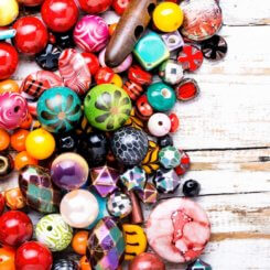A pile of colorful beads on a white wood background