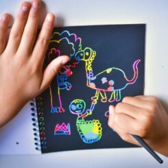 a picture of a child scraping sratch paper to reveal an image of a dinosaurs and other figures.