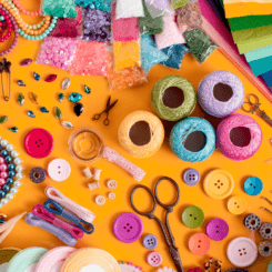 Lots of brightly colored craft supplies like scissors, yarn, beads, and jewels, strewn across an orange background..
