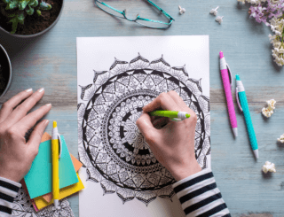 A woman begins to color a mandala coloring page with colored pencils.