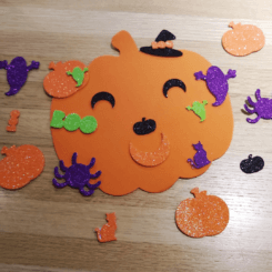 A foam pumpkin cut out surrounded by glittery stickers in Halloween motifs.