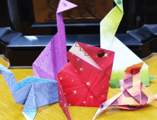 Five origami dinosaurs in brightly patterned paper.