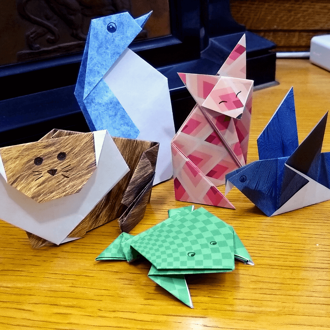 5 origami animals in patterned paper. A green jumping frog, tan lion, blue penguin, orange fox, and blue pigeon.