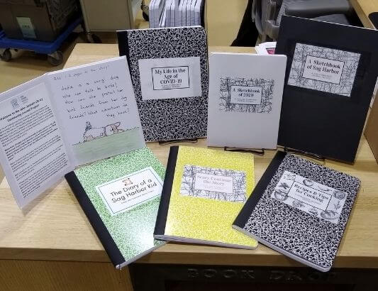 A collection of marble notebooks and sketchbooks on book stands.