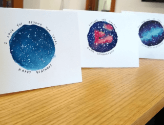 three cards with different galaxy paintings arranged on a shelf