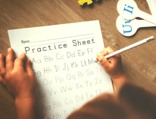 a child traces letters on a practice sheet with a pencil.