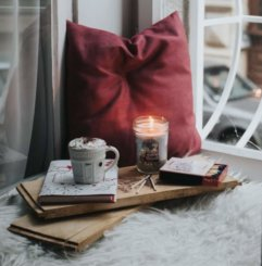 A cozy tray of a mug of coffee, a candle, a book, in a winter window seat.