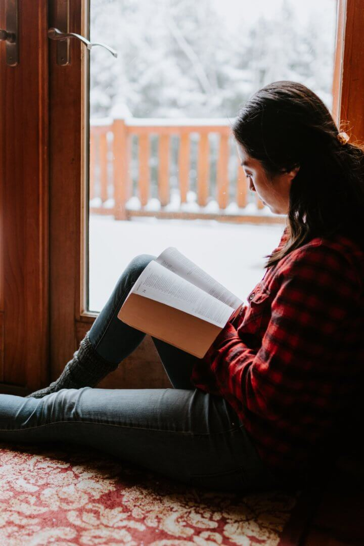 Woman in a red plaid shirt reading a book next to a window showing a snowy backdrop