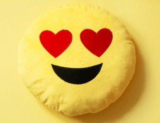 yellow smiley face emoji with hearts for eyes.