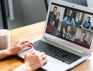 A person's hands are on a laptop where 6 people are on the screen in an online meeting.