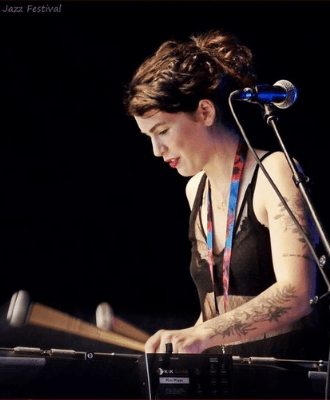 woman uses mallets to play a table-top instrument.