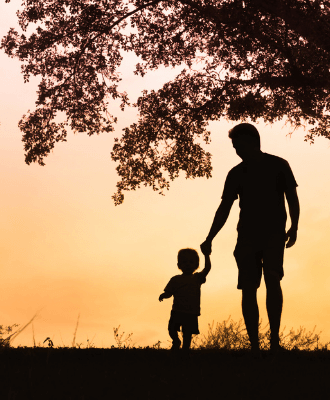 Silhouette of a man holding the hand of a toddler against a sunset and tree.